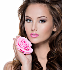 Face of a beautiful  woman with long brown hairs and pink flower