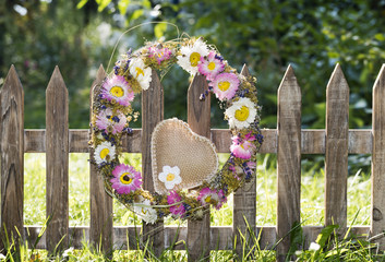 Blumenkranz mit Herz hängt an einem Gartenzaun