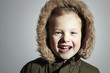 Smiling child in fur hood and coat.little boy winter style
