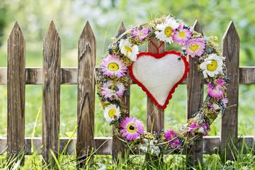 Blumenkranz mit Herz, hängt am Zaun