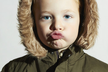 funny child in fur hood and winter jacket. fashion kids