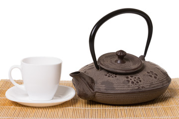 White cup of tea on saucer and iron teapot on wooden mat.