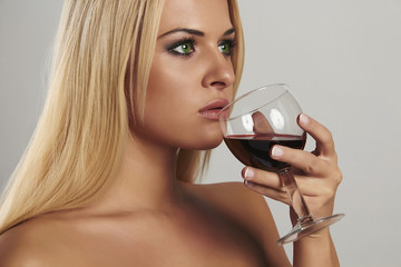 Beautiful blond woman drinking red wine.adult girl with alcohol