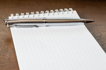 Pen and the notebook on wooden table