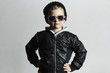 Fashionable little boy in sunglasses. Child in Black cap