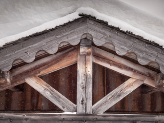 detail of aged woodwork in the eaves of a snow covered roof