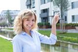 Junge Frau mit blonden Locken hat eine Wohnung gefunden