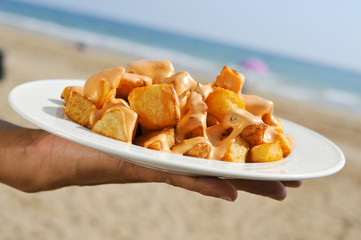 typical spanish patatas bravas, fried potatoes with a hot sauce,