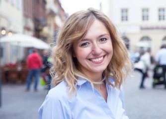 Junge Frau mit blonden Locken in einer Fussgängerzone