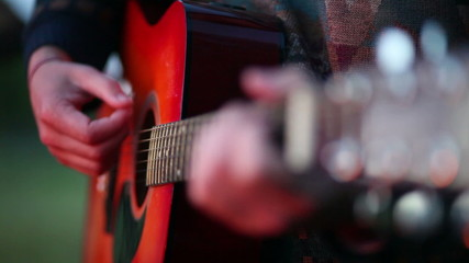 Closeup of a man playing on an acoustic guitar at a campfire