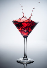 Red cocktail with splash on white