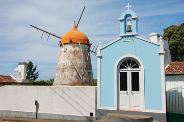 Red windmill and church in azores island