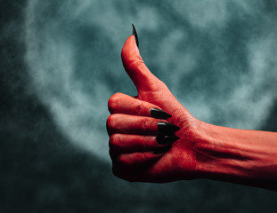 Devil hand with thumb up gesture at midnight