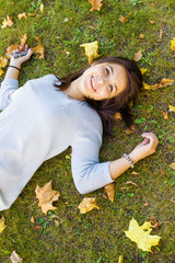 Tteen girl on a green lawn with yellow leaves lying on his back