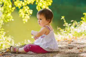 Baby girl sitting on the shore of the lake