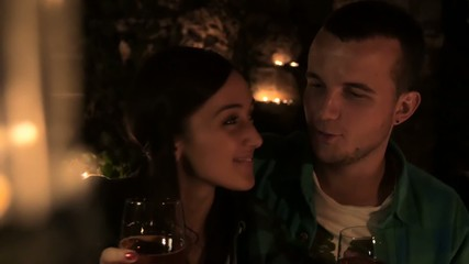 Young couple in love drinking wine by candlelight