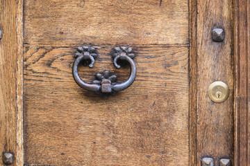 Ancient rusty door handle on brown old wooden door