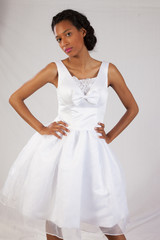 Black woman in white dress looking thoughtful
