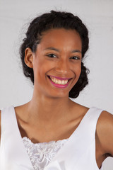 Black woman in white dress smiling