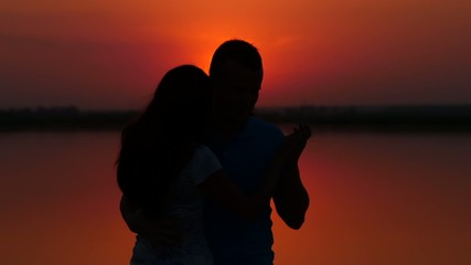Couple in love dancing salsa at sunset