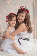 Girl hugs her little sister, both wearing red Christmas caps and