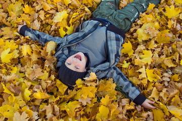 Ребенок смеется в осенних желтых листьях