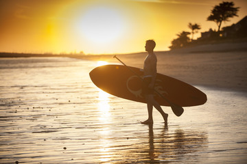 silhouette of a man with his paddle board on the beach at sunset