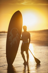 silhouette of a man with his paddle board standing on the beach