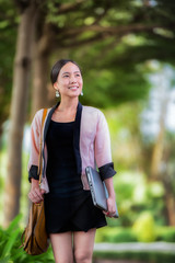 Pretty young asian woman walking with laptop under the hand