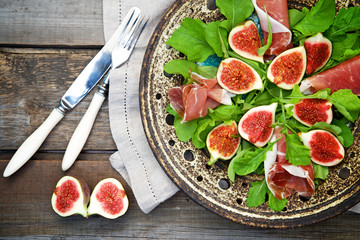 Appetizer consisting of figs, prosciutto ham and rocket salad