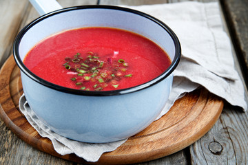 Beet soup in a pot on a wooden background