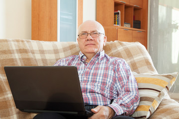 gray-haired man working at laptop