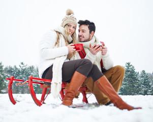 Paar im Winter trinkt Tee auf Schlitten