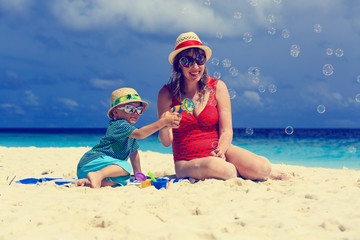 mother and son making soap bubbles on beach