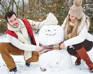 Paar baut Schneemann im Schnee