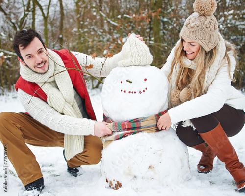 canvas print picture Paar baut Schneemann im Schnee