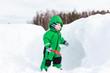 little boy digging winter snow