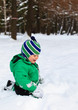 little boy playing with winter snow