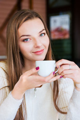Woman sitting in a cafe with cup of coffee