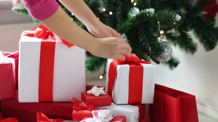 woman putting present under christmas tree