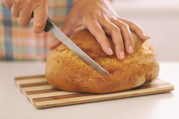 Woman's hands slicing bread