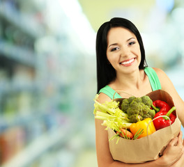 Shopping concept. Girl with package of food on shop background