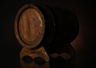Barrel on wooden table on dark background