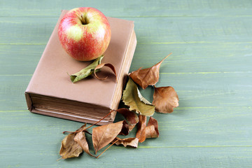 Apple with book and dry leaves on wooden background