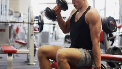 young man with dumbbells in gym