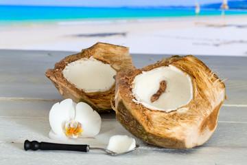 Kokosnuss am Strand mit Löffel und Orchidee
