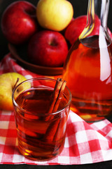 Apple cider in glass and bottle with cinnamon sticks and fresh