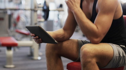 young man with tablet pc computer in gym