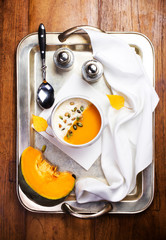 Beautiful autumn Pumpkin soup with cream in a white bowl with si