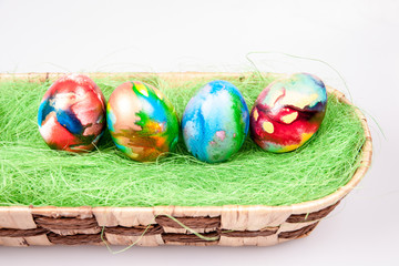 Colorful E|aster eggs in wicked bascet on a white background